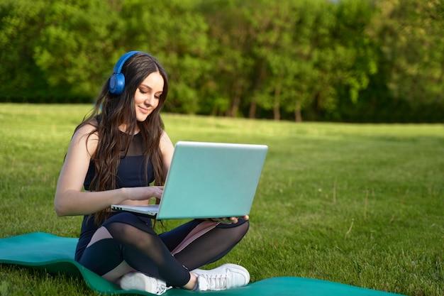 Une jeune fille aux cheveux longs portant des écouteurs est assise avec un ordinateur portable dans la nature