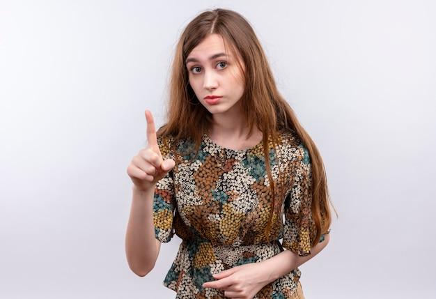 Jeune fille aux cheveux longs portant une robe colorée pointant l'index vers le haut d'avertissement avec un visage sérieux