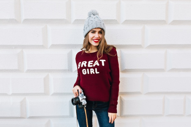 Jeune fille aux cheveux longs en pull marsala sur mur gris. elle porte un bonnet tricoté, tient la caméra et sourit.