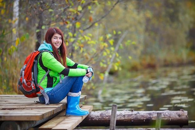 Jeune fille aux cheveux longs et touriste sac à dos