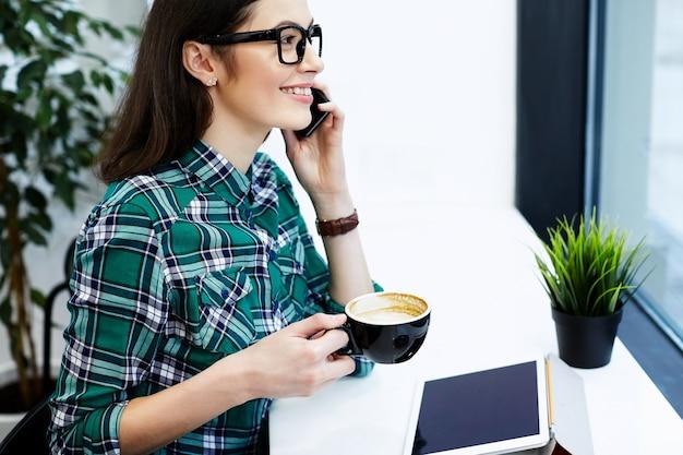 Jeune fille aux cheveux noirs portant chemise et lunettes assis dans un café avec tablette et tasse de café, parlant au téléphone mobile, concept indépendant, souriant.
