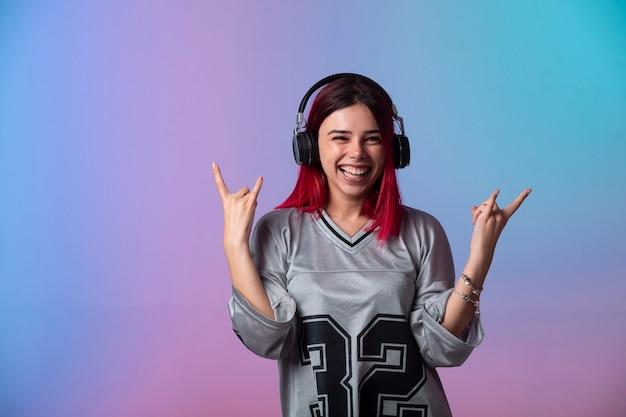Jeune fille aux cheveux roses a l'air positif et porte des écouteurs.