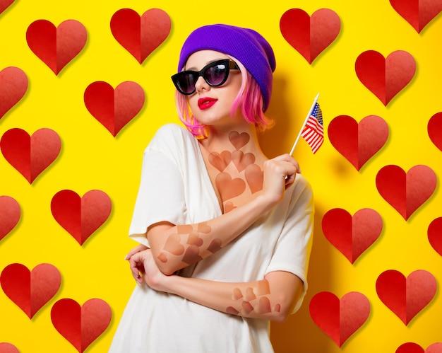 Jeune fille aux cheveux roses en chapeau violet et lunettes de soleil tenant le drapeau des états-unis sur fond jaune