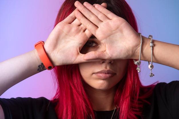 Jeune fille aux cheveux roses croisant ses mains sur son visage.