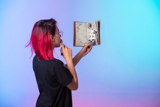 Jeune fille aux cheveux roses tenant un carnet de croquis et regardant.