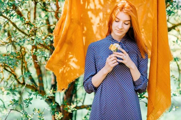 Jeune fille aux cheveux rouges avec des fleurs à la main et une couverture orange derrière elle