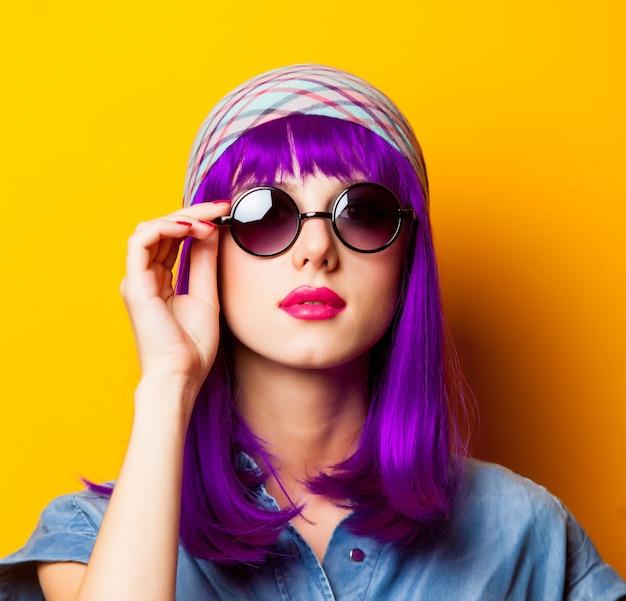 Jeune fille aux cheveux violets et lunettes de soleil sur jaune