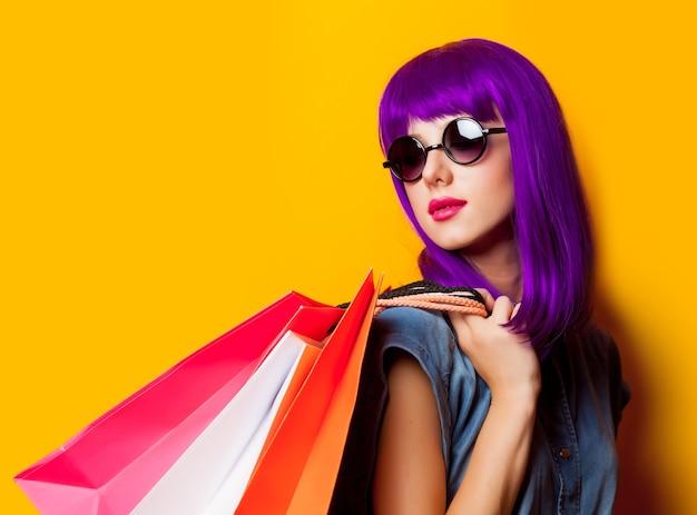 Jeune fille aux cheveux violets et sacs à provisions sur jaune
