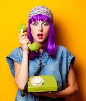 Jeune fille aux cheveux violets avec téléphone vintage sur jaune