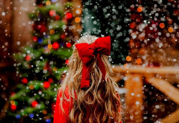 Jeune fille aux longs cheveux blonds bouclés avec noeud rouge de noël debout par son dos sur fond de noël sous la neige.