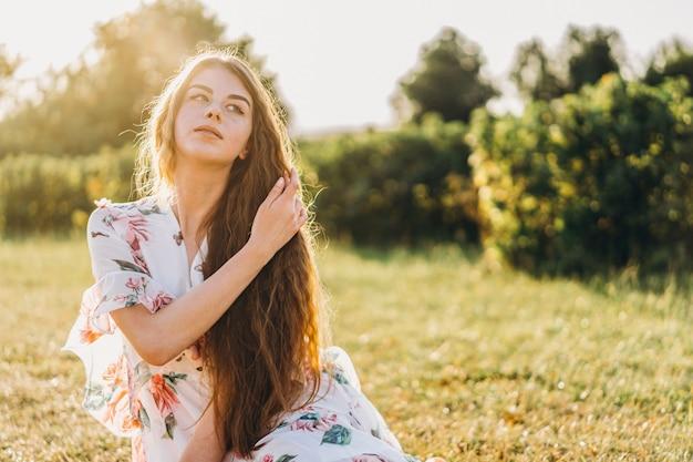 Jeune fille aux longs cheveux bouclés, brune, visage en taches de rousseur, avec maquillage et yeux verts, en robe blanche légère posant