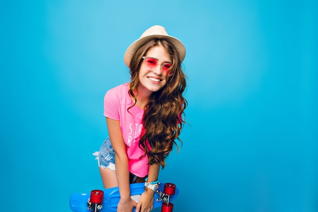 Jeune fille aux longs cheveux bouclés dans des lunettes de soleil roses posant sur fond bleu en studio. elle porte un short, un t-shirt rose, un chapeau. elle tient une planche à roulettes bleue et sourit à la caméra.