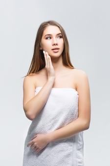 Jeune fille aux sourcils épais et peau parfaite au mur blanc, serviette sur le corps