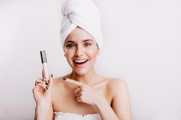 Une jeune fille aux yeux verts dans une serviette blanche avec un sourire indique un correcteur cachant toutes les imperfections de la peau.
