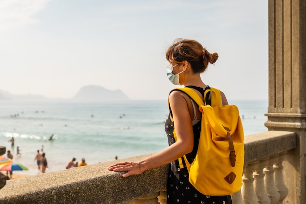 Jeune fille aventureuse avec masque facial et sac à dos jaune regardant la plage