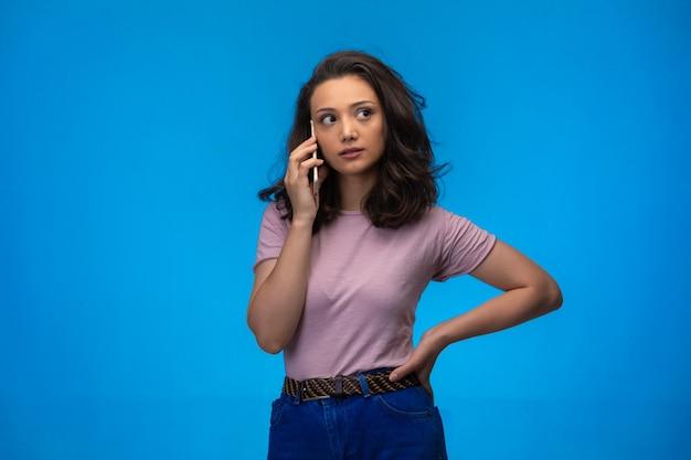 Jeune fille ayant appelé son smartphone tout en mettant sa main à sa taille.