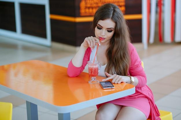 Jeune fille ayant un soda tout en regardant son téléphone