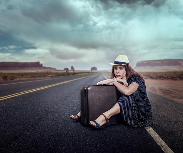 Jeune fille avec des bagages voyageant en auto-stop.