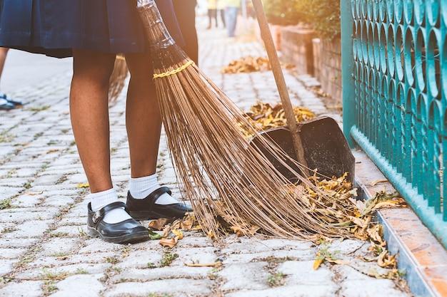 Jeune fille balayant les feuilles séchées sur le sol à l'école.
