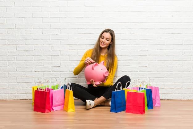 Jeune fille avec beaucoup de sacs en prenant une tirelire et heureuse parce qu'elle est pleine