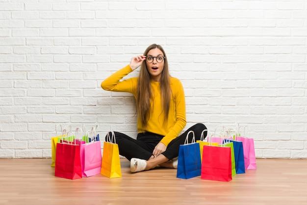 Jeune fille avec beaucoup de sacs à provisions avec des lunettes et surpris