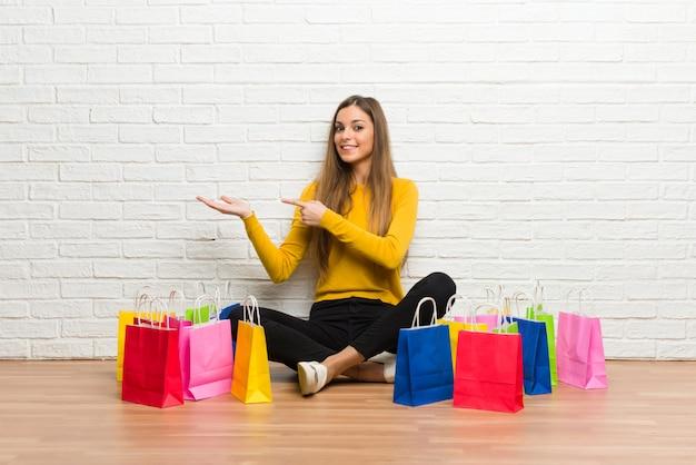 Jeune fille avec beaucoup de sacs à provisions tenant une surface imaginaire sur la paume pour insérer une annonce