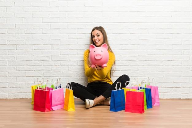 Jeune fille avec beaucoup de sacs à provisions tenant une tirelire