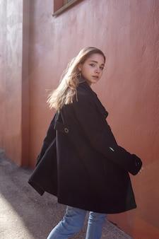 Jeune fille belle aux cheveux longs en manteau noir par une journée ensoleillée se retourne contre le mur rouge. portrait de rue