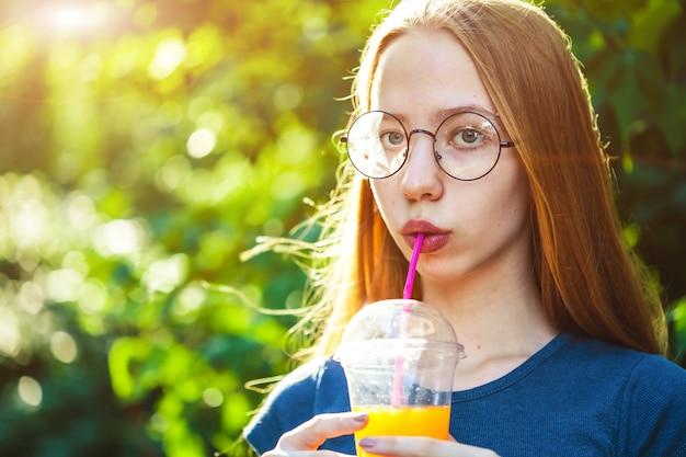 Jeune fille belle boit du jus fraîchement pressé sur un fond.