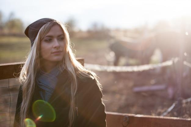 Jeune fille belle dans une écurie, en plein air, photo avec tons chauds, rayons de soleil