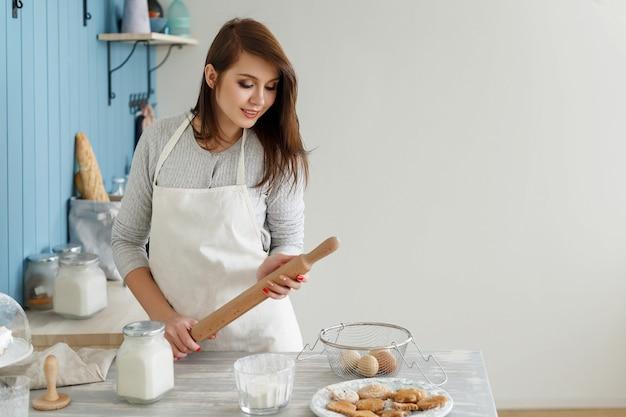 Jeune fille belle dans un tablier, faisant les biscuits de pâte