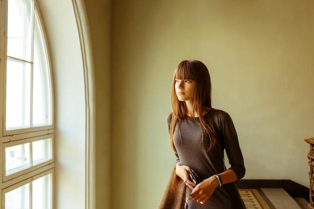Jeune fille belle, debout près de la fenêtre en souriant.