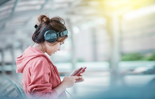 Jeune fille belle écoute de la musique avec ses écouteurs dans la rue en une journée ensoleillée d'été