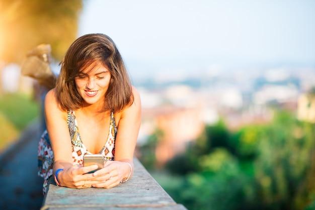Jeune fille belle sur un mur dans une ville envoie un message avec le réseau social de son téléphone