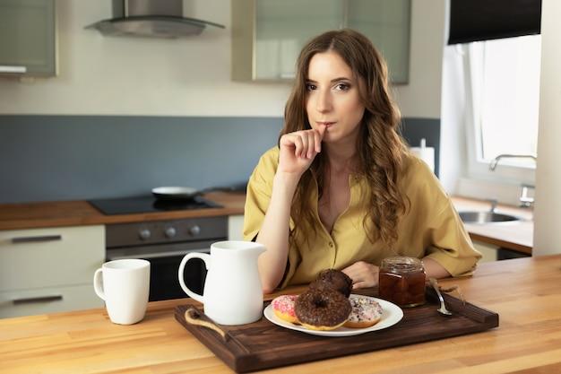 Jeune fille belle, prenant son petit déjeuner à la maison dans la cuisine. la fille mange des aliments malsains et riches en calories.