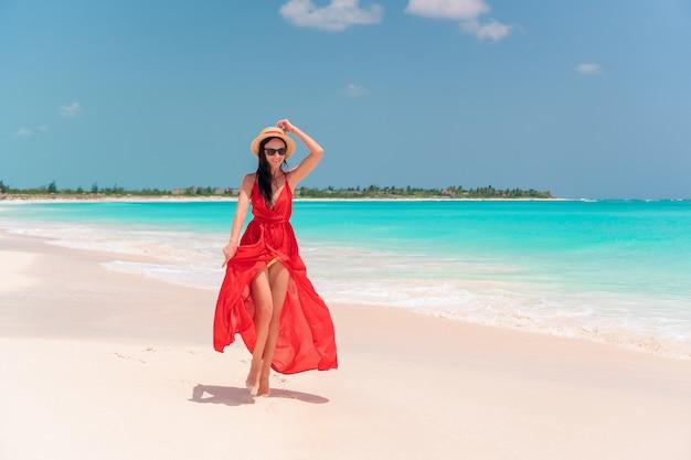 Jeune fille en belle robe rouge au bord de la mer