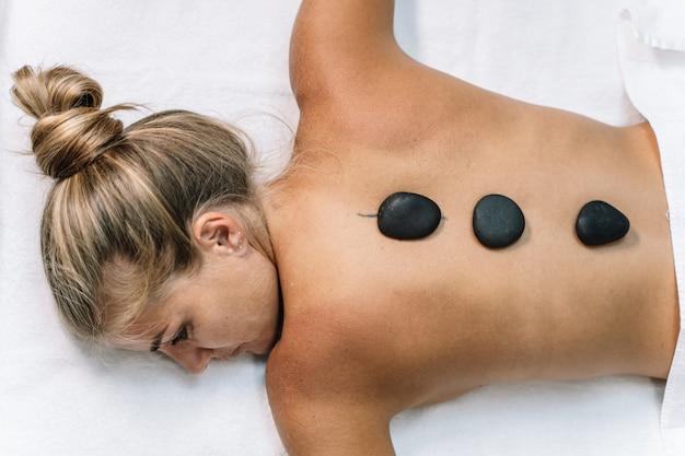 Jeune fille blonde allongée sur une serviette blanche avec des pierres noires sur le dos