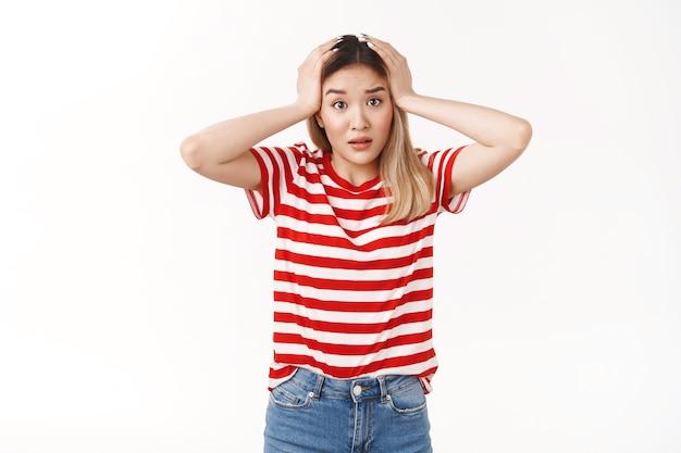 Une jeune fille blonde asiatique perplexe s'empare de la tête en train de paniquer, confus, qu'est-ce que l'appareil photo a l'air inquiet face à une situation terrible, réagissant nerveusement aux mauvaises nouvelles, haletant anxieux, debout sur un mur blanc