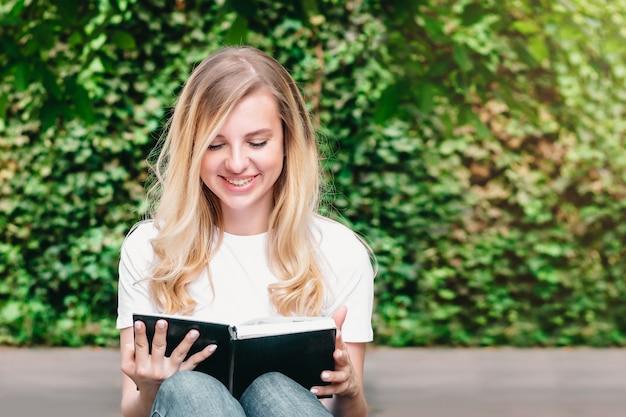 Jeune fille blonde assise sur un banc, lit un livre et sourit dans un parc
