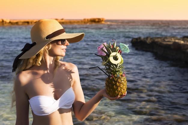 Jeune fille blonde au chapeau tenant un ananas à la plage au coucher du soleil