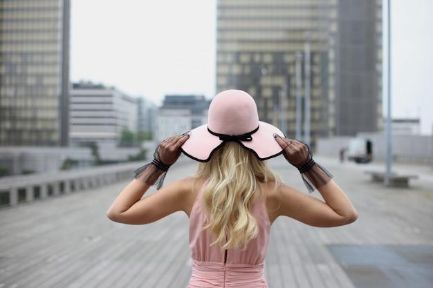 Une jeune fille blonde aux cheveux longs dans un chapeau rose et des gants noirs recule