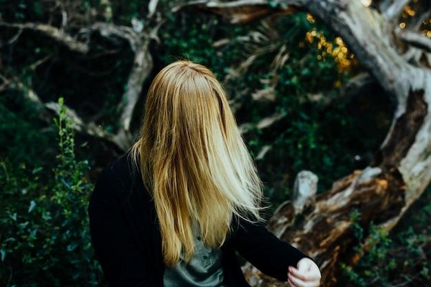 Jeune fille blonde aux longs cheveux raides cache son visage avec ses cheveux, anonyme.