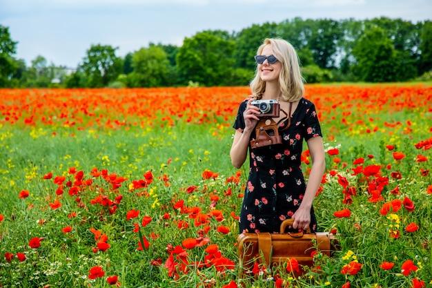 Jeune fille blonde en belle robe avec appareil photo et valise dans le champ de coquelicots en été