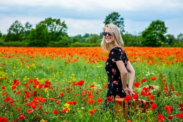 Jeune fille blonde en belle robe avec valise dans le champ de coquelicots en été