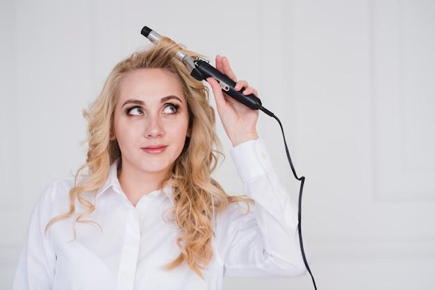 Jeune fille blonde bouclant ses cheveux