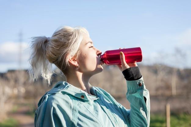 Jeune fille blonde buvant de l'eau pendant le jogging matinal
