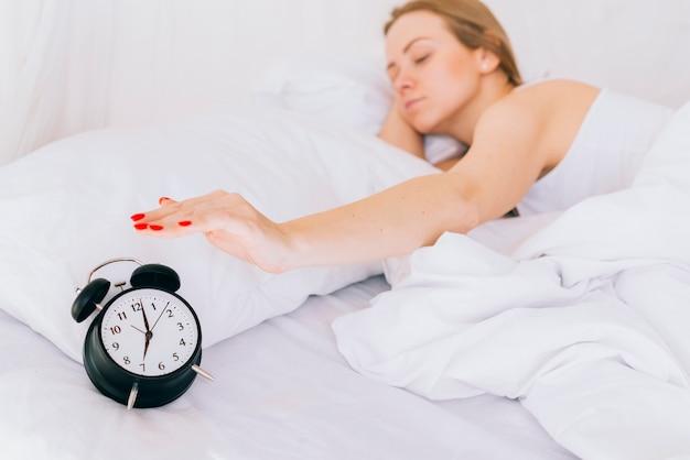 Jeune fille blonde déclencher l'alarme de l'horloge