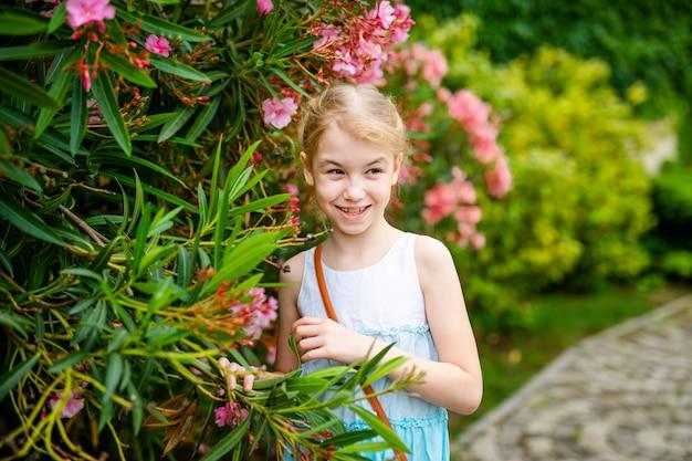 Jeune fille blonde avec deux tresses en robe blanche et bleue restant parmi les arbres verts et les buissons