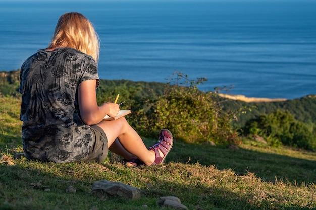 Une jeune fille blonde écrit ses pensées dans un journal personnel sur la montagne avec vue sur la mer, profitez de votre temps et de vos moments de voyage et de détente