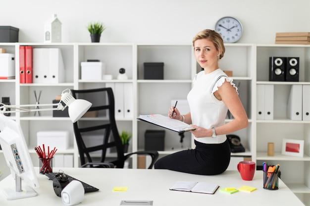 Une jeune fille blonde est assise à son bureau et tient des documents et un crayon.